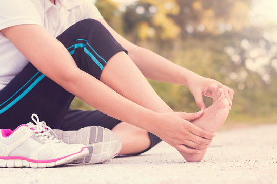 Young woman massaging her painful foot from exercising and runni
