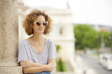 Summer day in the city. Close-up portrait of young confident woman wearing sunglasses and smiling.