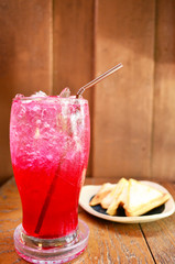 Red soda water with Sandwich on wood background