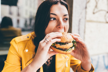 Young woman sitting in a restaurant eating an hamburger hand hold- hunger, food, meal concept