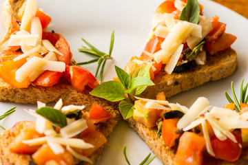 Bruschetta - Bruschetta with sliced tomatoes salad and olive with herb topping.