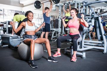 Frauen und Männer haben Spaß beim Sport und Fitness im Fitnessstudio