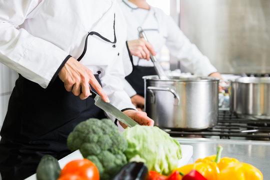 Team von Köchinnen beim Zubereiten von Gerichten in einer Kantinen-Küche