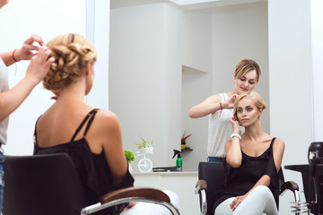 Female hair stylist braids her beautiful client's hair in front of the mirror at the beauty salon. Beauty industry concept.