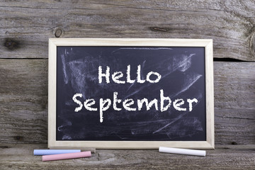 Hello September. Old wooden background with texture and chalk bl