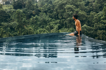 Man sitting on the edge of infinity pool at resort