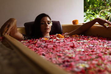 Young woman relaxing in floral bath at spa