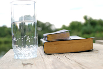 glass of water  close to the book, the Bible