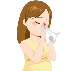 Young pregnant woman with flu sneezing on tissue