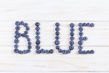 Word blue written letters with blueberries on white wooden board