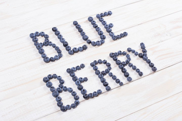 Word blueberry written letters with blueberries on white wooden