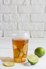 Iced tea in a plastic cup with straw with slice of lime. White w