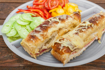 Tasty sandwich with ham, melted cheese and vegetables