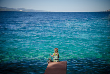 girl sitting on a bridge overlooking the sea