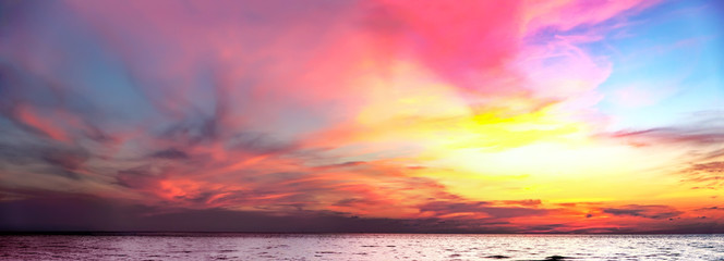 Tropical colorful dramatic sunset with cloudy sky. Evening calm on the Gulf of Thailand. Bright afterglow.