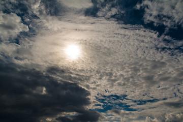 Sun hidden behind a veil of clouds.