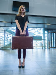 Girl with vintage retro suitcase in airport terminal