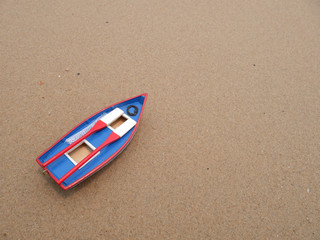 Wooden toy boat on the beach