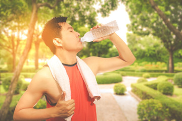 asian handsome young jogger drinking water after hard exercise in the garden