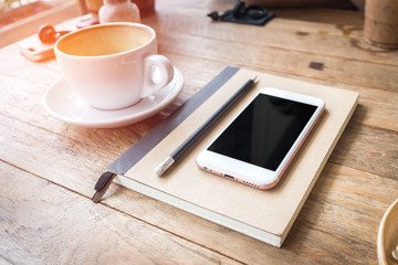 Mobile phone and diary notebook with coffee cup on wood backgrou