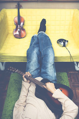 unidentified asian man playing guitar & lying on the floor for music lover or cozy living lifestyle concept