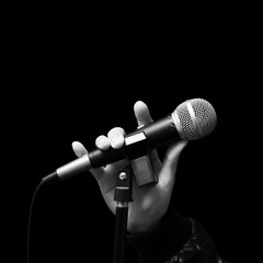 singer right hand holding dynamic microphone, bw filter & isolated on black ( hand sign mean love ) concept = love to sing