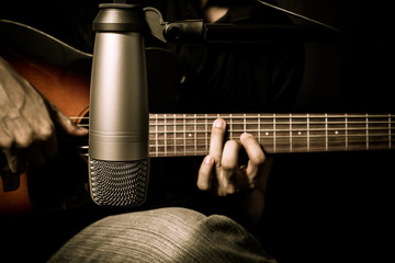 male musician playing acoustic guitar behind condenser microphone in recording studio