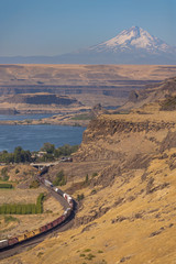 Maryhill, Washington. Maryhill is named after the wife and daughter of regional icon Sam Hill. A train runs through the area along the Columbia River and Mt. Hood can be seen in the background.