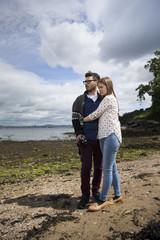 Young couple walking along pebble beach.