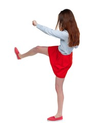 skinny woman funny fights waving his arms and legs. Long-haired brunette in red skirt swung a leg.