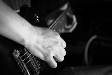 musician hands playing electric guitar, black and white