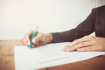 Businesswoman's hand with pen completing personal information on