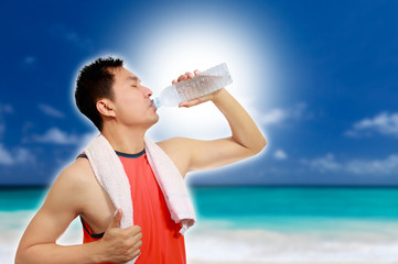thirsty young asian handsome athlete drinking water on the beach in summer