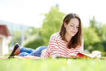 Full length portrait of a smiling beautiful young woman reading a book in the park.