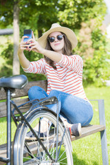 Full length shot of a beautiful young woman taking selfie with her mobile phone while relaxing outdoor.