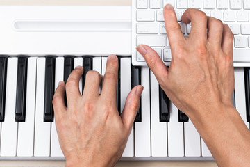professional asian composer hands making songs on piano keys & computer for music production concept