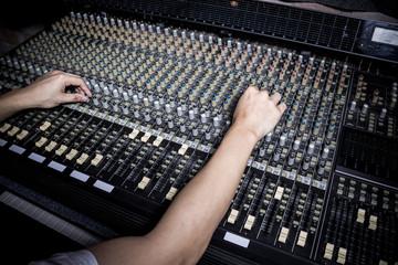 hands of sound engineer working on recording studio mixer