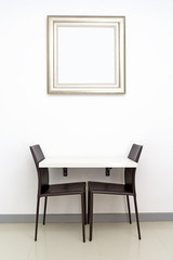 white table, black leather chairs & silver picture frame on white wall background for small space interior concept
