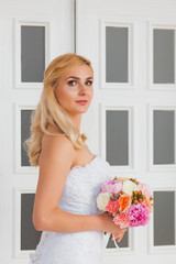 Portrait of a beautiful blonde bride with bouquet in an interior light, wedding concept