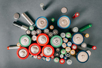 Colorful batteries on gray background, top view. Energy bright backdrop, close-up