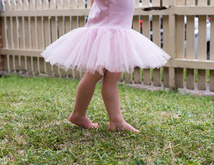 Toddler girl in pink tutu  dancing on grass in front garden with picket fence (cropped)