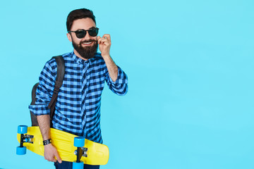stylish hipster man in shirt over blue background with copyspace