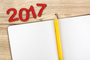 Top view of 2017 new year red number with blank open notebook an