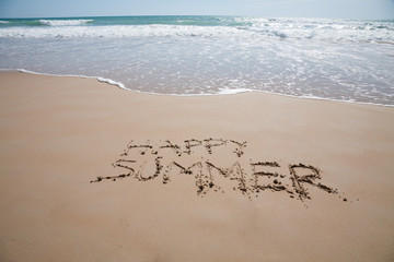 happy summer text written on brown sand ground at beach with ocean seashore in horizon in Spain Europe