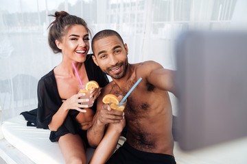 Multiracial couple making selfie and holding cocktails at the beach