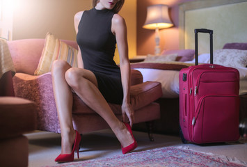 Classy lady wearing red stilettos in her hotel room
