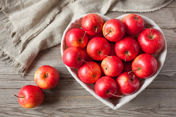 Red apples in the basket heart shape on wooden background