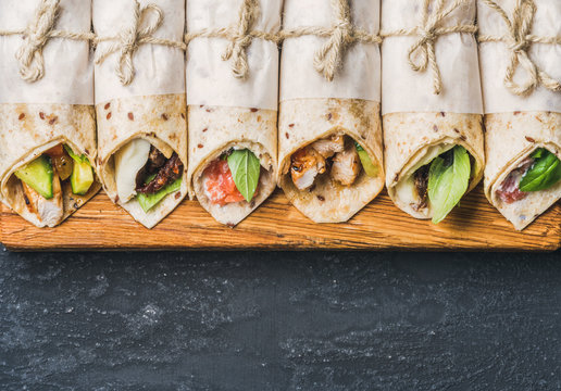 Tortilla wraps with various fillings on wooden board over dark grey grunge concrete background, top view, copy space, horizontal composition. Healthy snack or take-away lunch bites