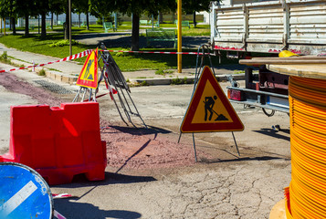 Warning signs for work in progress on road under construction. .fiber optic cables buried in a micro trench with concrete colored red by a worker