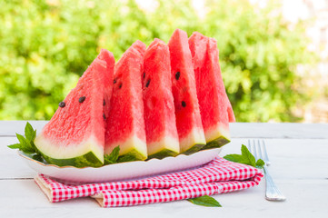 Slices of watermelon in a plate on wooden table